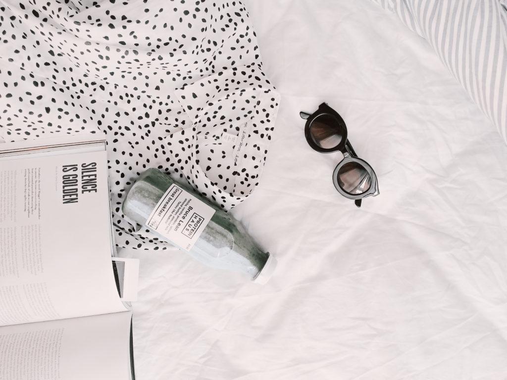 Buch, Bluse, Sonnenbrille und Saft