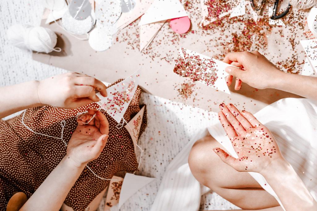 Frauen, die gerade mit Glitzer dekorieren